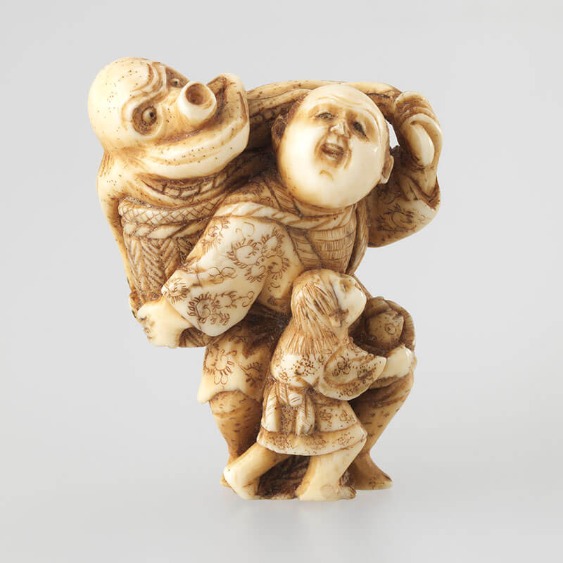 Unknown, Japan / Netsuke: (fisherman with a large octopus emerging from a basket and child at his knee) 19th century