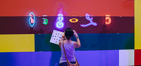 A Gallery visitor photographs Michael Parekowhai's <em>Home Front</em> 2015 at GOMA, Mar 2015 / Gift of the artist and Michael Lett through the Queensland Art Gallery | Gallery of Modern Art Foundation 2015 / Photograph: Brodie Standen