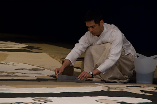 Lee Mingwei installing Gernika in sand at the Gallery of Modern Art, 2008