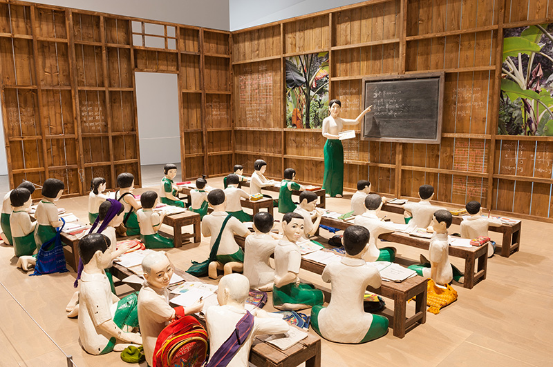 Nge Lay, Myanmar b.1979 / The sick classroom 2013 / 27 wooden sculptures, timber walls, 8 desks, 26 student accessories, 1 table, 1 chair; 15 photographs, eds. 1/5; single-channel video, ed. 1/5 / Purchased 2015. Queensland Art Gallery | Gallery of Modern Art Foundation / Collection: Queensland Art Gallery / © The artist